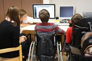 Projektteilnehmende mit und ohne Rollstuhl vor dem Computer