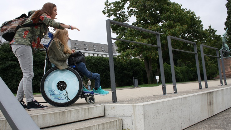 Mädchen im Rollstuhl vor einer Treppe
