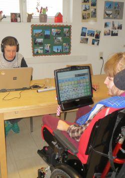 Junge Frau mit Talker und Junge mit Kopfhörer am Laptop