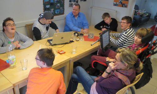 Junge Menschen mit und ohne Behinderung sitzen zusammen um einen Tisch