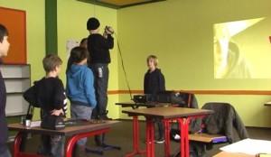 Junge filmt, auf dem Tisch stehend, anderen Jungen in Draufsicht. An die Wand hinter ihnen wird Ergebnis gebeamt.