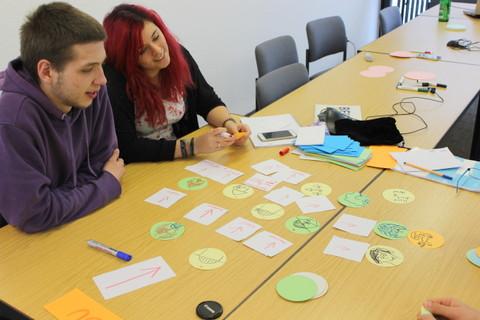 Junger Mann und junge Frau am Schreibtisch, Piktogramme für das Zauberspiel bastelnd