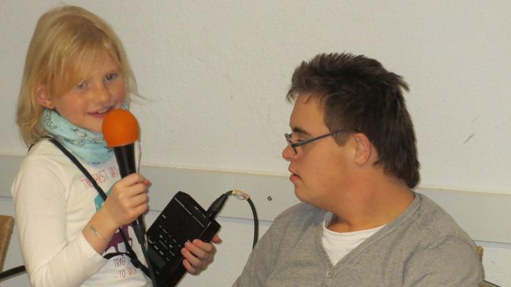 Mädchen mit Mikrofon und Aufnahmegerät und älterer Junge