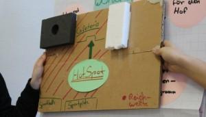 Gebastelter Prototyp wird präsentiert, um Idee für Umgang mit Handys in Schule zu präsentieren.