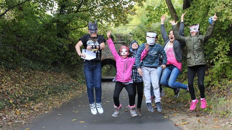 Junge Menschen springen in die Luft, einige haben Masken auf