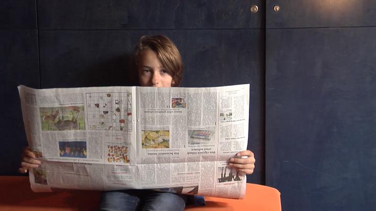 Filmausschnitt: Junge hinter Zeitung