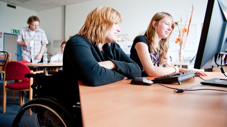 Zwei Mädchen vor dem Computer, ein Mädchen nutzt einen Rollstuhl