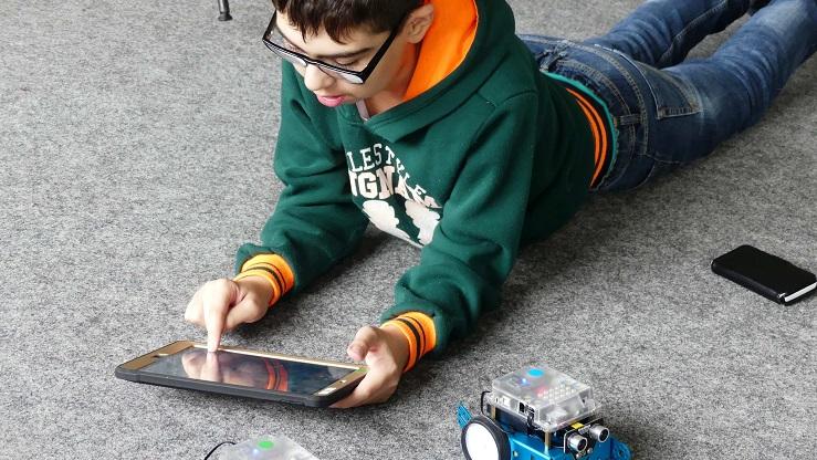 Junge steuert Mini-Roboter mit Tablet