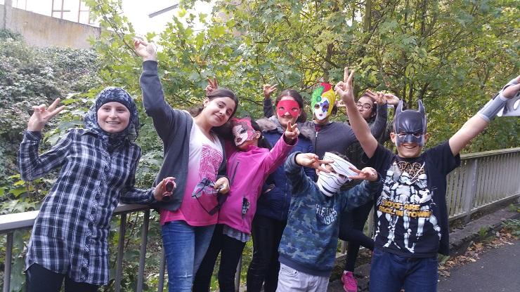 Kinder mit Migrationshintergrund mit bunten Masken