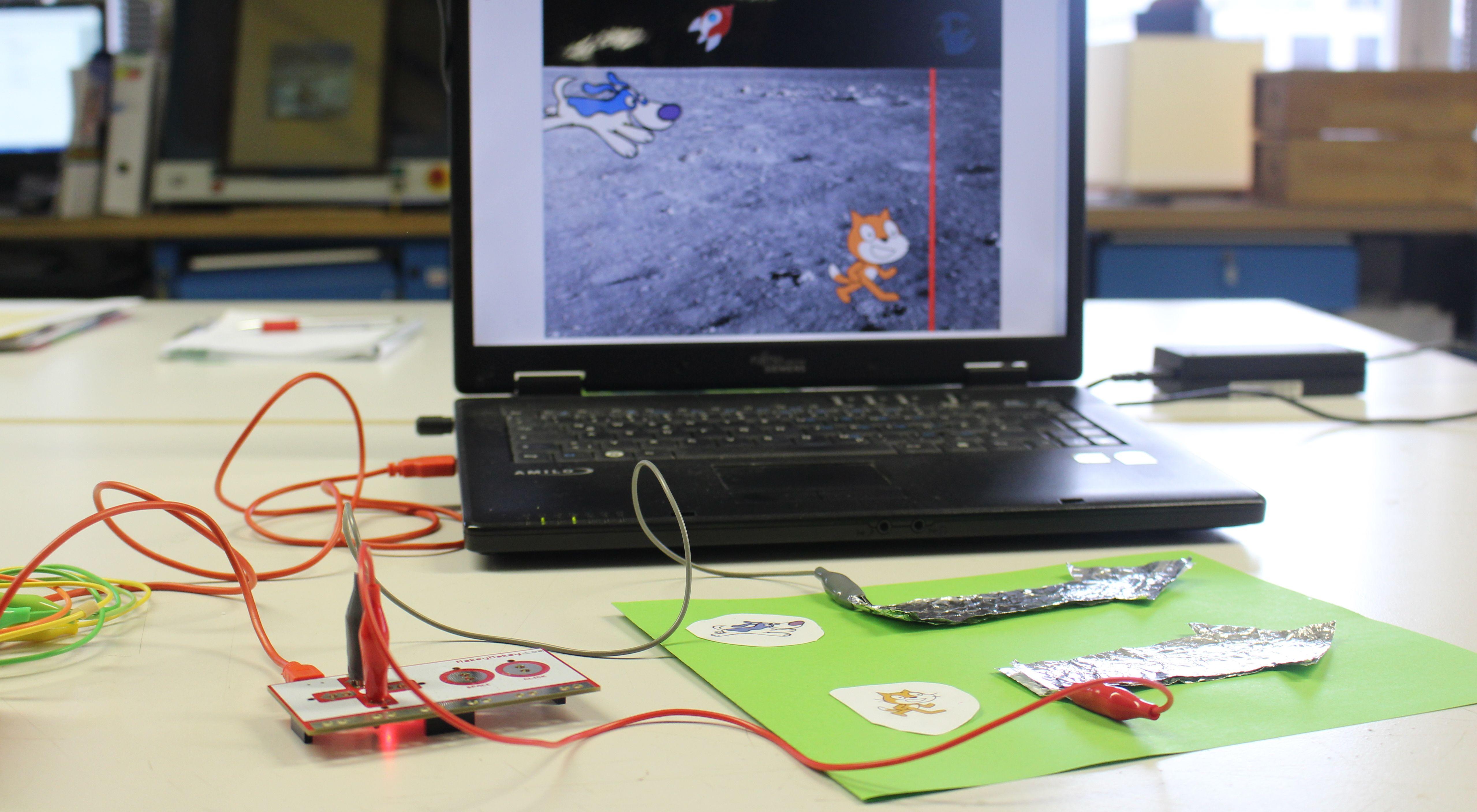 Laptop mit Scratch-programmierten Computerspiel mit selbstgebauten MaKey-MaKey-Controller: Zwei Pfeile aus Aluminiumfolie angeschlossen an die Steuerplatine