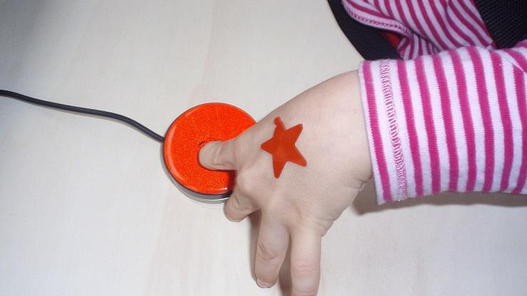 Kinderhand, die auf Taster drückt