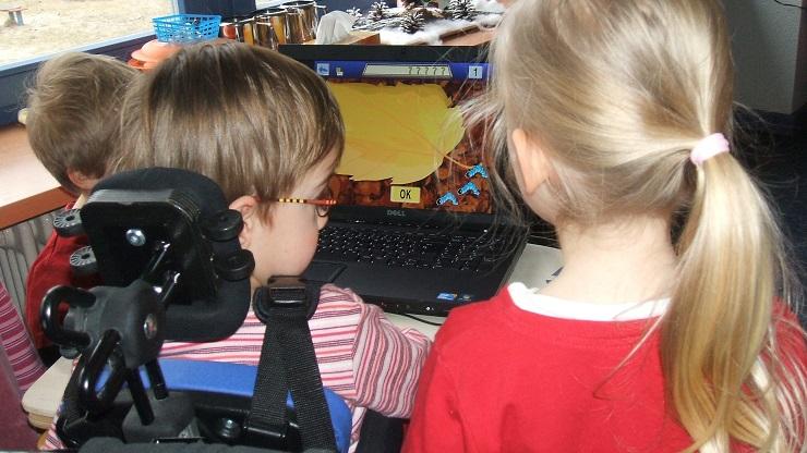 Kind im Rollstuhl vor Computerspiel