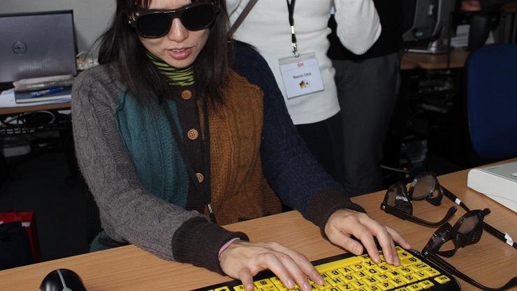 Japanische Frau testet Sehbehindertentastatur mit Sehbehinderungsimulationsbrille