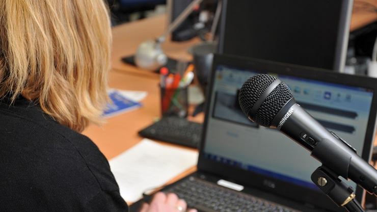 Frau vor Schnittprogramm mit Mikrofon