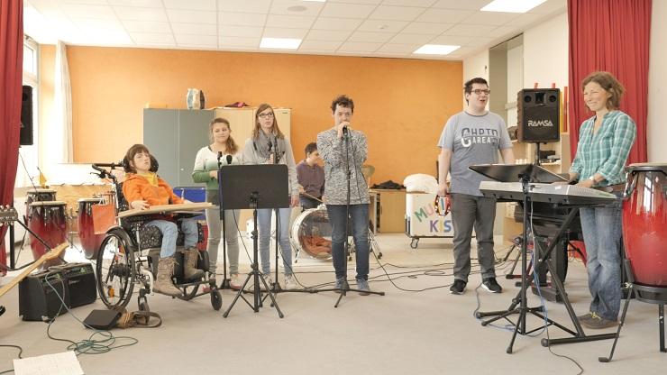 Schüler*innen mit Körperbehinderung spielen in einer Band