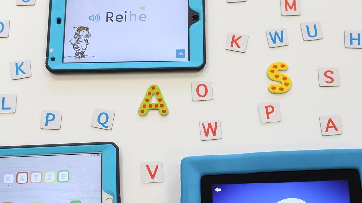 Tablets mit Lese-Apps vor weißem Hintergrund mit bunten Buchstaben