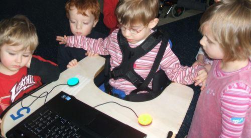 Kinder am Computer, ein Kind im Rollstuhl nutzt Taster, um den Computer zu bedienen