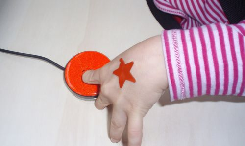 Kinderhand auf buntem Taster