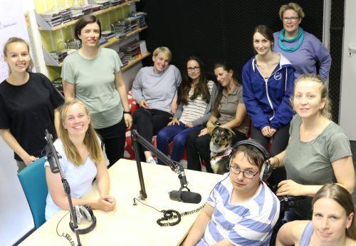 Die Radio-Inklusive-Redaktion vor Aufnahmegeräten, lächelnd. Ein junger Mann im Rollstuhl und 10 Frauen.