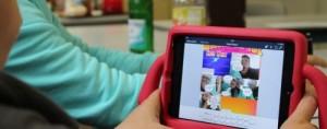 Junge hält iPad in pinker iPad-Halterung in der Hand, zu sehen ist ein Comic auf dem Bildschirm