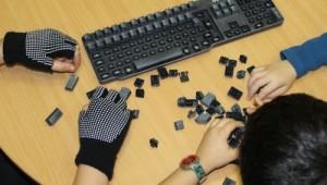 Kinder bauen bei einer alten Tastatur die Tasten aus