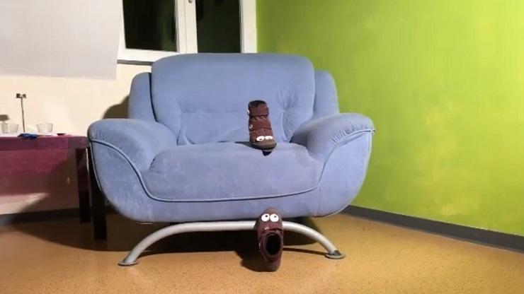 Filmausschnitt: Zwei Kinderschuhe mit aufgeklebten Augen kletten auf ein Sofa