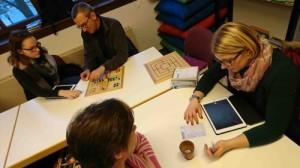 Teilnehmer des Schachcafés fotografieren Gesellschaftsspiele mit Tablets
