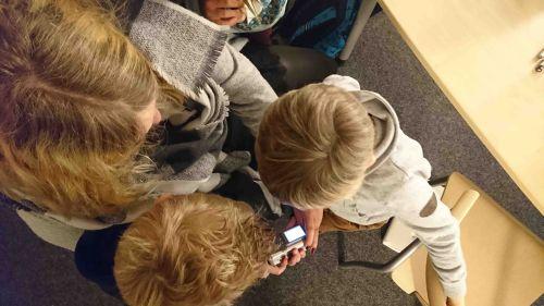Zwei Kinder lassen sich von einer Erzieherin die Bedienung der Kamera erklären