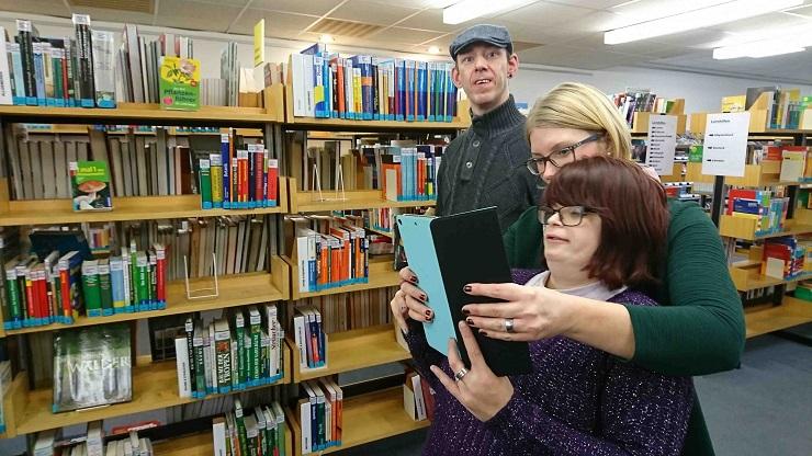 Frau fotografiert mit Tablet in Bibliothek, sie wird unterstützt von einer Assistenz. Ein Mann schaut in die Kamera
