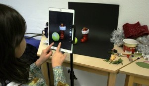 Mädchen fotografiert mit Tablet Weihnachtsmotive vor schwarzem Hintergrund