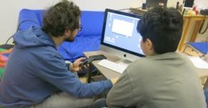 Mann und Jugendlicher vor Bildschirm