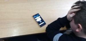 Junge schlägt seine Hände vor das weinende Gesicht, vor ihm ein Smartphone auf dem Tisch liegend