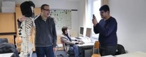 Junge fotografiert lachenden Jungen, der ein Skelett mit einer Fellmütze in einem Klassenzimmer umarmt. Im Hintergrund ein weiterer Junge am PC