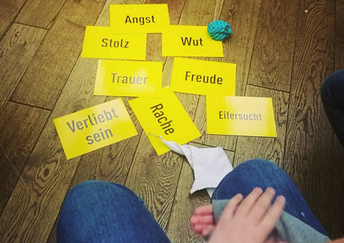 Auf dem Boden Karten mit Emotionen. Auf einer Karte ein Ball. Davor eine Person, sitzend.