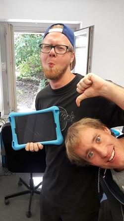 Zwei junge Männer, grinsend. Einer hält ein iPad mit gecrashten Display in der Hand und zeigt Daumen runter.