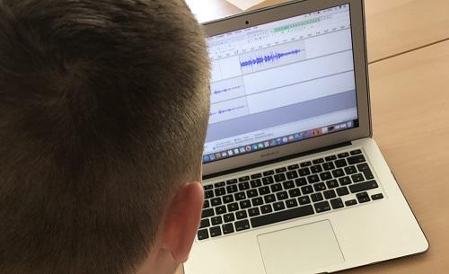 Junge vor Laptop mit geöffnetem Audioschnittprogramm