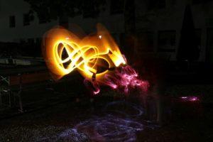 Lightpainting-Foto: Lichtmotiv aus gelben und roten Licht vor schwarzem Hintergrund