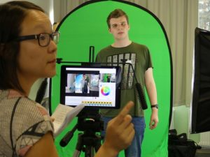 Junge Frau fotografiert mit Tablet auf Stativ Jugendlichen vor dem Greenscreen