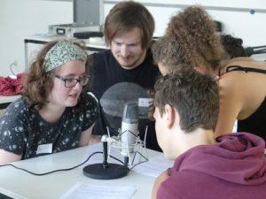 Ein Mädchen und ein Junge sprechen in ein Mikrofon, sie werden von einem Medientrainer und einer Medientrainerin unterstützt