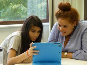 Melanie Leusch von der Inklusiven OT Ohmstraße zeigt einem Mädchen etwas auf einem iPad mit blauer Hülle
