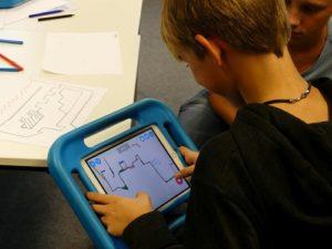 Ein Junge spielt ein selbstgemaltes und mit der App Draw Your Game erstelltes Computergame