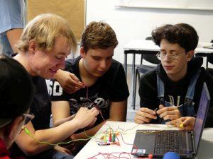 Jungen und Medientrainer vor Laptop, sie halten die Krokodilklemmen der MaKey MaKey Platine in den Händen