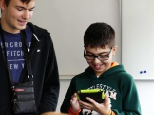 Ein Jugendlicher zeigt einem Jungen etwas auf dem Tablet