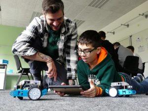 Johannes Rück erklärt einem auf den Boden liegenden Jungen, wie er mBot-Roboter mit der App mBlockly steuern kann