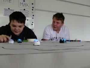 Zwei Jungen verfolgen, wie blinkende ozobot-Roboter den selbstgemalten Strichcodes folgen