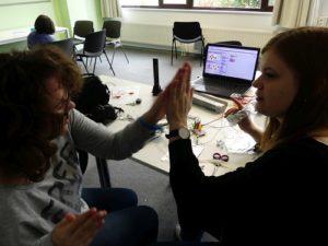 Junge Frau und Mädchen geben sich High-Five, während die eine die MaKey MaKey-Platine in den Händen hält