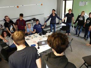 Teilnehmende des inklusiven Jugendmediencamps stehen in einem Kreis und fassen sich an den Händen