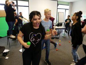 Mädchen und Jungen des inklusiven Mediencamps laufen mit bunten Bällen in der Hand durcheinander