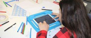 Mädchen vor iPad in blauer dicker Hülle und vielen bunten Stiften