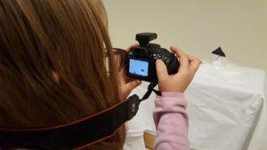 Kind fotografiert mit Spiegelreflexkamera gebastelten Schneemann